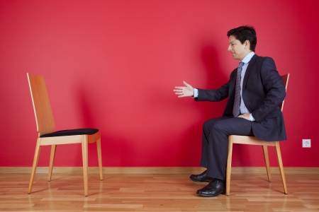 Handshake agreement between a businessman and an chair next to a red wall photo
