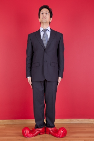 clown shoes: Happy businessman next to a red wall with clown shoes