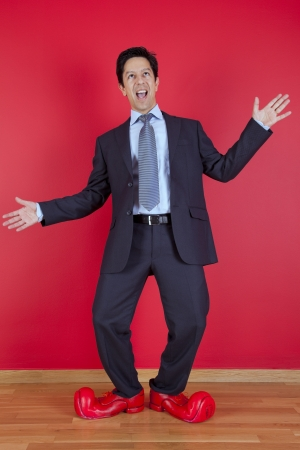 Happy businessman next to a red wall with clown shoes Stock Photo - 16373613