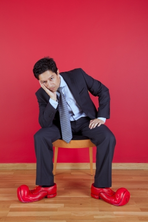 clown shoes: Businessman sited next to a red wall with clown shoes