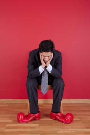 Businessman sited next to a red wall with clown shoes Stock Photo - 16389208