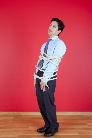 Businessman tied up with a rope struggle to get free Stock Photo - 16389160