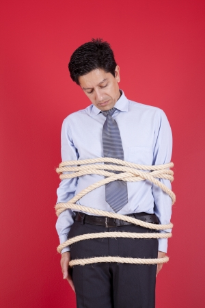 Businessman tied up with a rope struggle to get free Stock Photo - 16389311