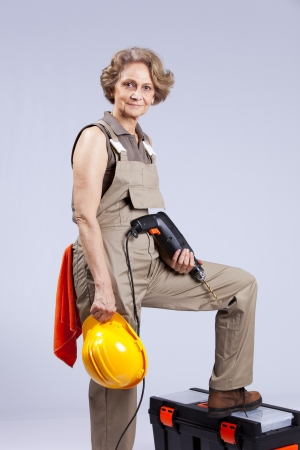 female construction worker: Happy senior woman holding a drill tool (isolated on gray) Stock Photo