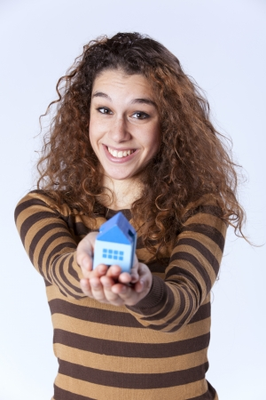 Happy young woman showing a small blue house Stock Photo - 16388735