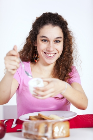 Young beautiful woman eating her morning yogurt photo