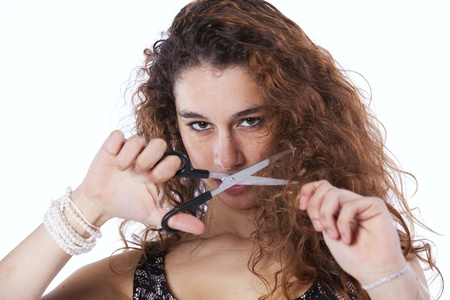 scissors hair: Unhappy woman cutting her hair with a scissor