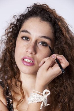 Beautiful young woman applying the eyeliner Stock Photo - 16389261