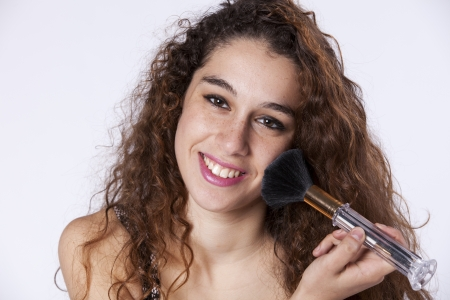 Happy beautiful woman applying some powder brush in her face Stock Photo - 16389145
