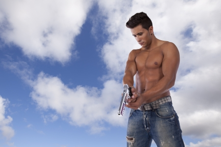 Powerful young man with a gun pointing down Stock Photo - 16387453