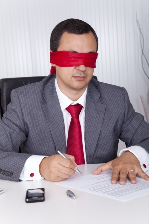 Blindfold businessman at the office working signing a contract photo