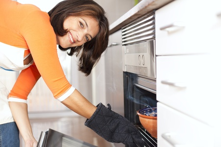 happy modern woman open the kitchen oven photo