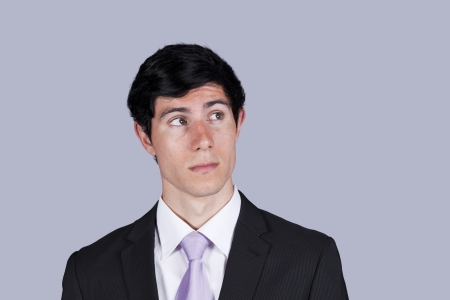 Young businessman thinking and looking up (isolated on gray) photo
