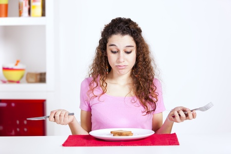 frustrated woman at her breakfast with only a toast on her plate Standard-Bild