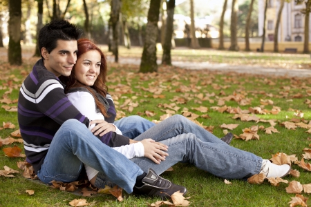 sit around: Love and affection between a young couple at the park in autumn season (selective focus with shallow DOF)