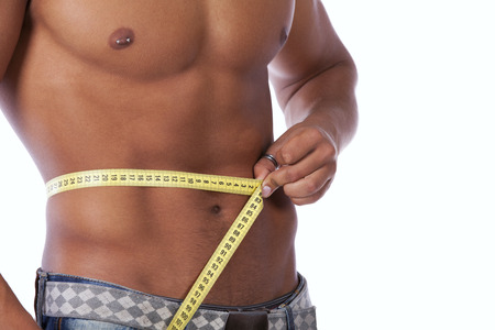 Men with perfect abs measuring his waist photo