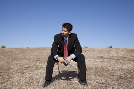 Businessman sit in a chair in outdoor with a handgun photo