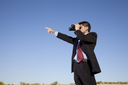 Businessman in outdoor looking though binoculars  photo