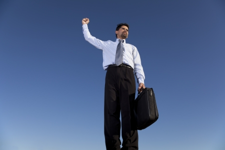 Successful businessman holding a briefcase in outdoor photo