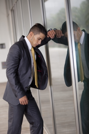 banging: frustrated businessman banging his head at the office window Stock Photo