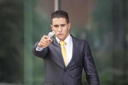 Powerful security businessman aiming a gun