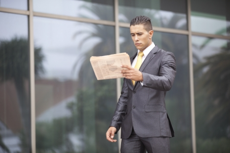 Businessman reading his newspaper next to his office building photo