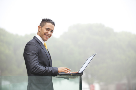 Confident young businessman working with his laptop at the office balcony Stock Photo