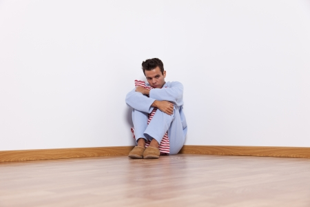Young man with nightclothes sit at the room corner with fear photo