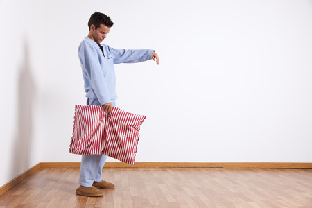 somnambulism: Young man sleepwalking at his home dress with nightclothes (isolated on white) Stock Photo