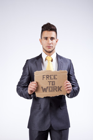 trouble free: Young businessman holding a piece of cardboard saying Free to Work Stock Photo