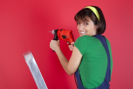 electric drill: Happy woman holding an electric drill