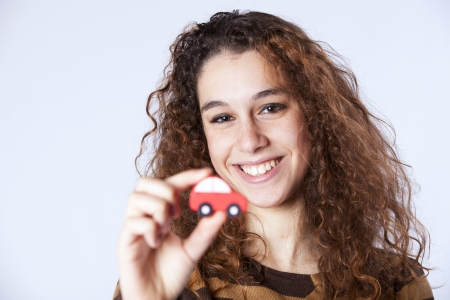 Happy young woman showing a small red car  photo