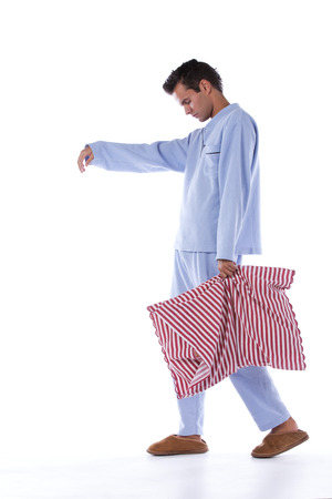 Young man sleepwalking dress with nightclothes (isolated on white) photo