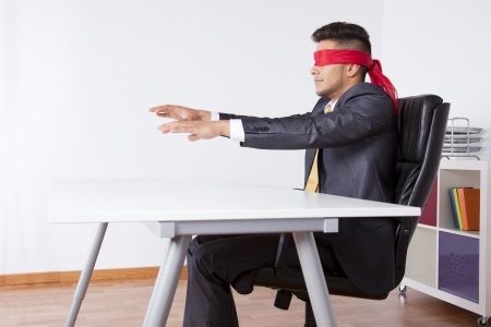 censure: Businessman at his office with scarf covering his eyes Stock Photo