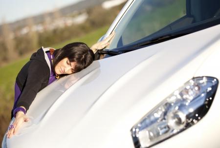 Beautiful woman embracing her new car photo