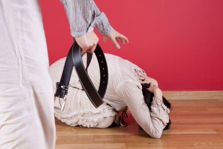 Men threating and beating his wife at home with a belt photo