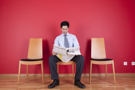 distrustful: businessman reading the newspaper siting on a chair Stock Photo