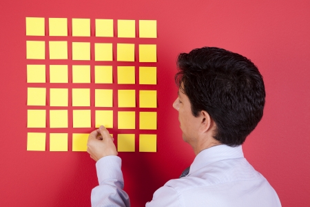Businessman looking to yellow papers sticked at a red wall Stock Photo - 23489046