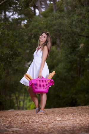 beautiful young woman in the woods with a basket full of bread photo