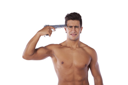Stressed young man with a gun pointing to his head (isolated on white) photo