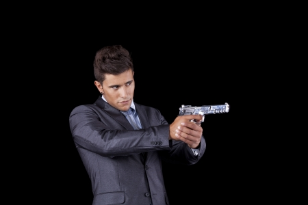 Powerful businessman with a gun (isolated on black) photo