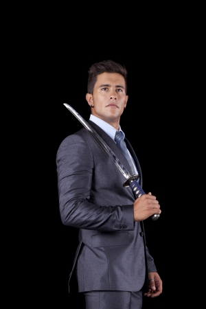 Powerful businessman holding a ninja sword (isolated on black) photo