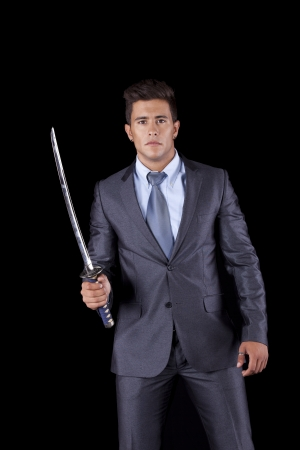 Powerful businessman holding a ninja sword (isolated on black) photo