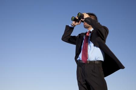 Businessman looking through his binoculars in outdoor
