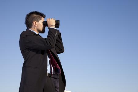 binoculars view: Businessman in outdoor looking though binoculars