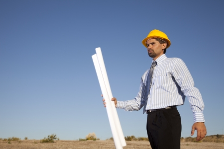 Businessman with blue prints at the field photo