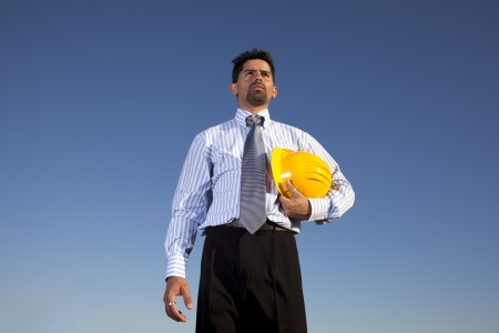 Engineer holding a construction helmet in the outdoor photo