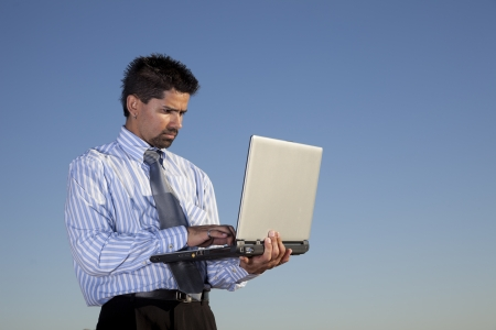 Businessman holding a laptop in outdoor photo