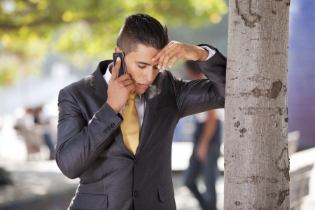 phone conversation: businessman with problems talking at his cellphone next to a tree