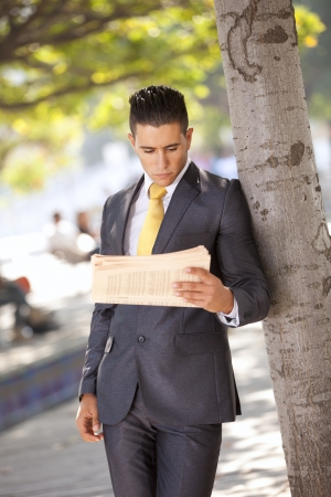Businessman reading the newspaper at the city park photo